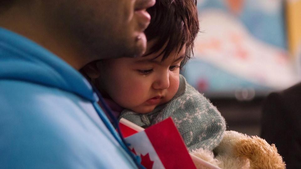 Une petite fille dans les bras de son père qui tient un petit drapeau canadien