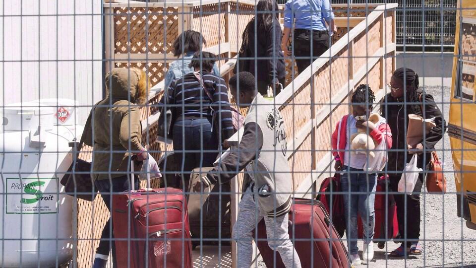 Un groupe de demandeurs d'asile arrive, valises à la main, aux installations d'hébergement temporaire au poste-frontière à Saint-Bernard-de-Lacolle, Québec, le mercredi 9 mai 2018.