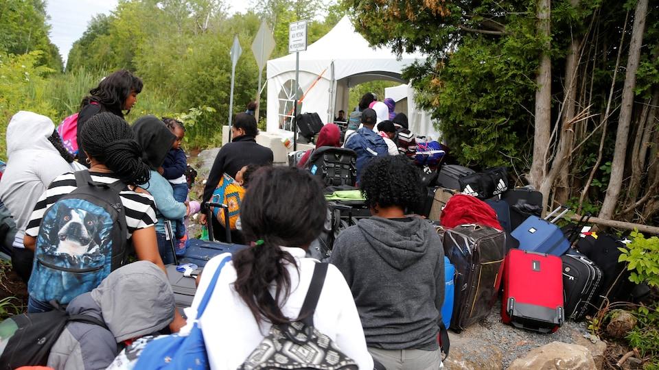 Cette photo prise la semaine dernière montre une file de demandeurs d'asile qui attendent de franchir un point de contrôle installé au bout du chemin Roxham, à Saint-Bernard-de-Lacolle.