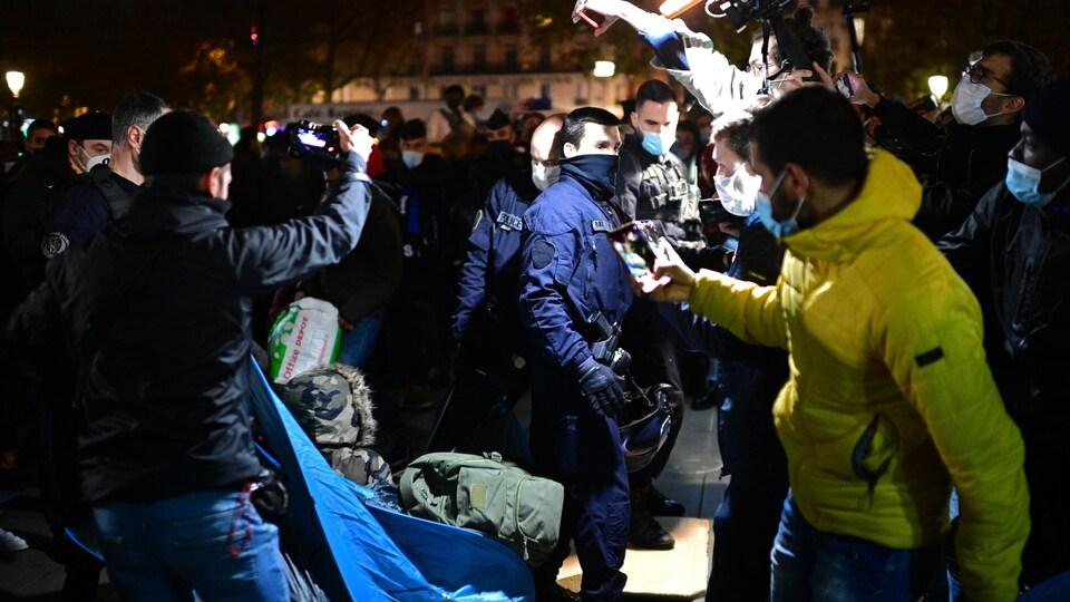 Des hommes filment des policiers avec des téléphones cellulaires.