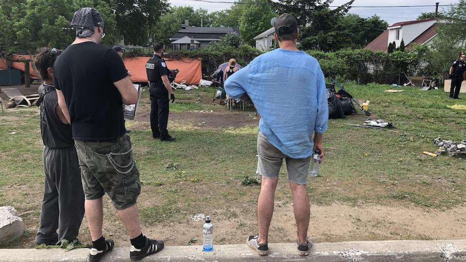 Trois hommes regardent des policiers démanteler le campement installé sur un terrain gazonné.