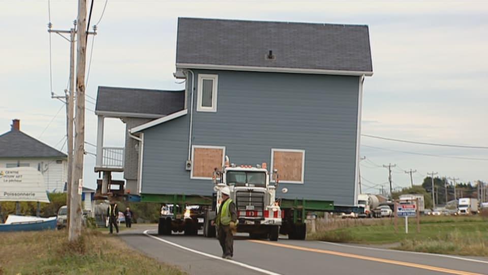 Une maison bleue est transportée par camion.