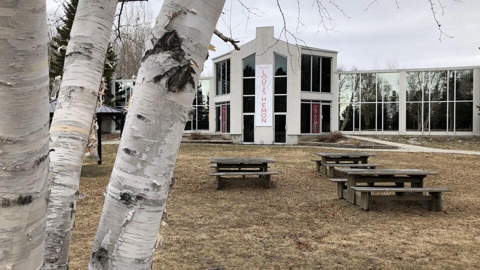 La devanture du Musée Louis-Hémon. On voit un arbre et des tables à pic-nic en avant-plan.