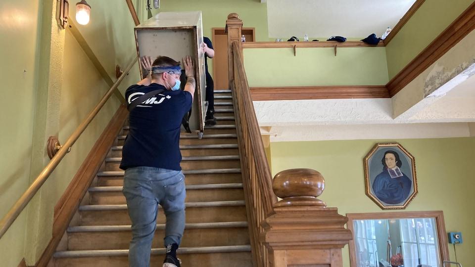 Des déménageurs descendent un escalier en transportant un meuble.