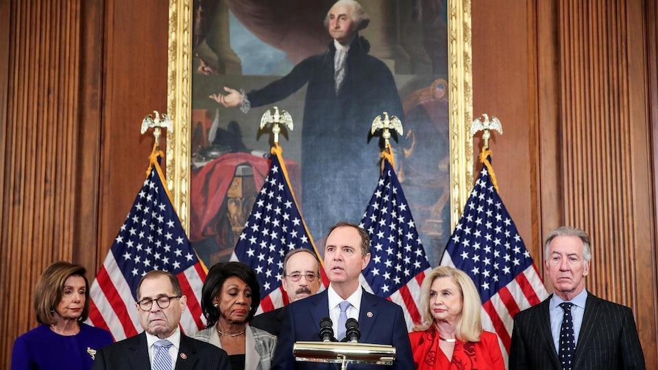 Sept dirigeants démocrates, dont Adam Schiff, qui parle devant un micro, tiennent une conférence de presse avec en arrière-plan quatre drapeaux américains et le portrait de George Washington.