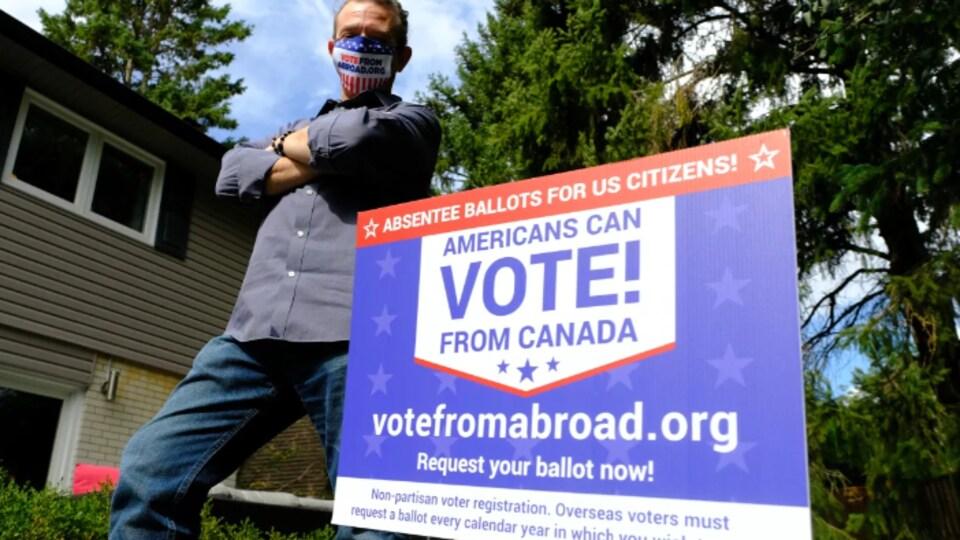 Steve Nardi à côté d'une pancarte incitant à voter.