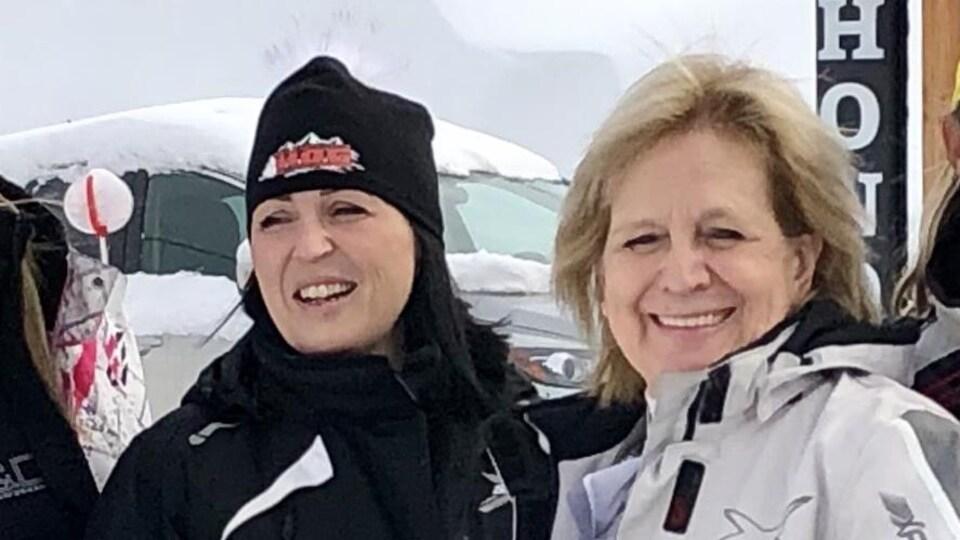 Photographiées à l'extérieur, les deux femmes sourient à la caméra.