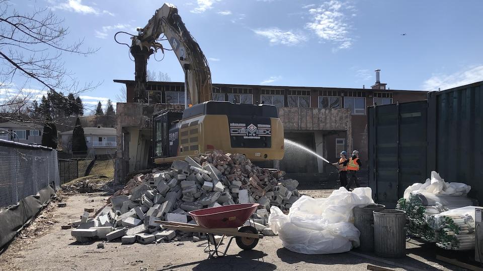 Une pelle mécanique détruit une école.