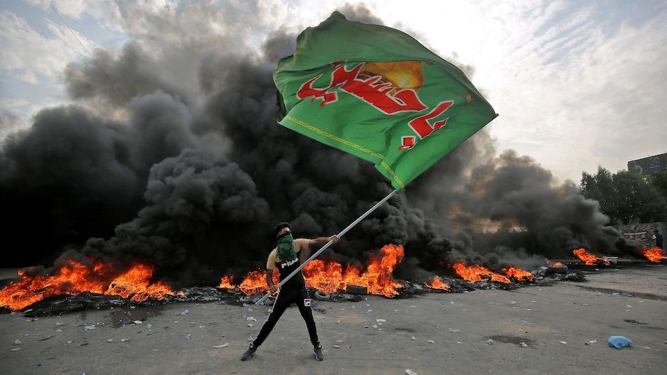 Un manifestant brandit un drapeau devant un immense incendie.