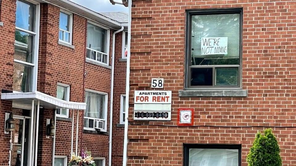 Des immeubles à logements abordables. Sur une fenêtre, on peut lire : « Je ne déménagerai pas. »