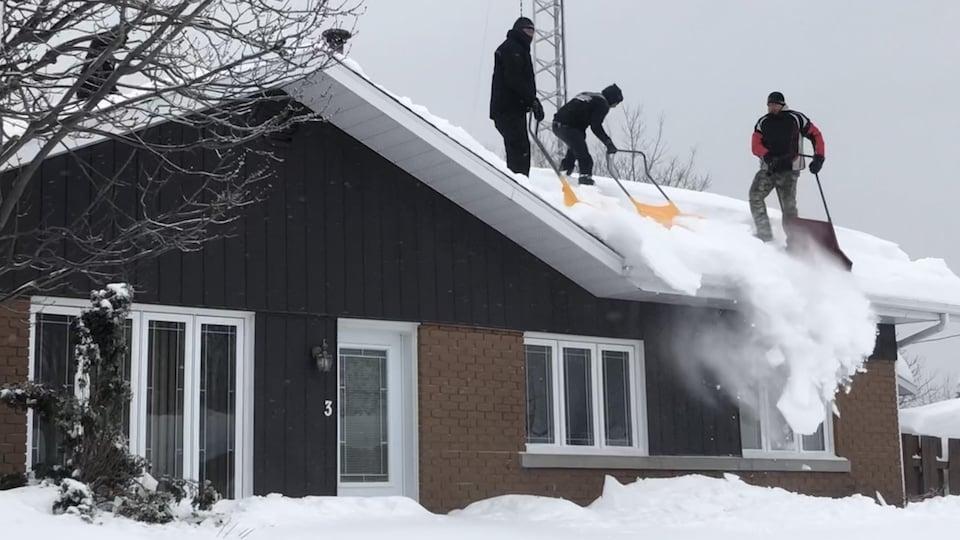 Des gens déneigent une toiture à Trois-Rivières