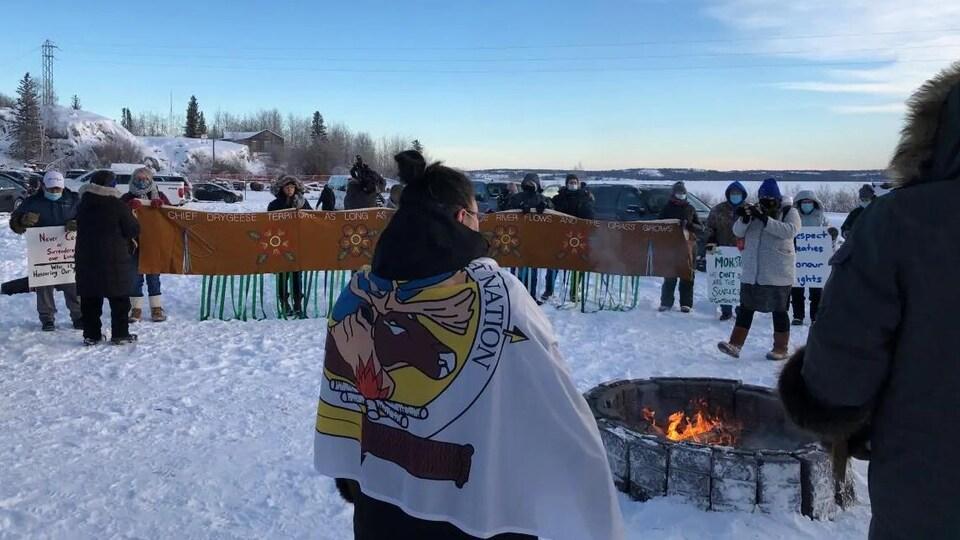 Des gens tenant des bannières autour d'un feu.