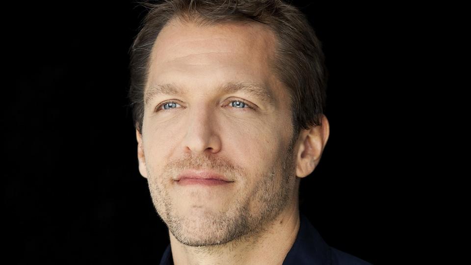 L'homme, qui se tient légèrement de profil devant la caméra, porte une chemise au bleu aussi profond que ses yeux.