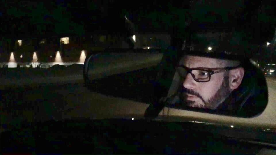 Le reflet d'un homme dans un rétroviseur.