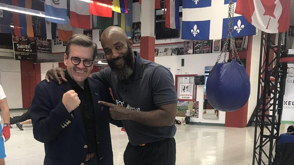Les deux hommes bras dessus, bras dessous dans un gymnase.
