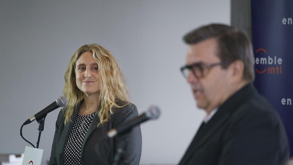 Karine Boivin Roy regarde parler Denis Coderre en souriant.