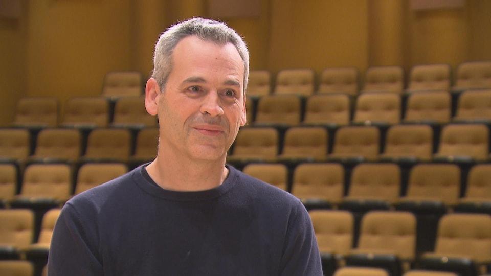 Un homme, avec les cheveux gris, assis devant les estrades d'une salle de concert.