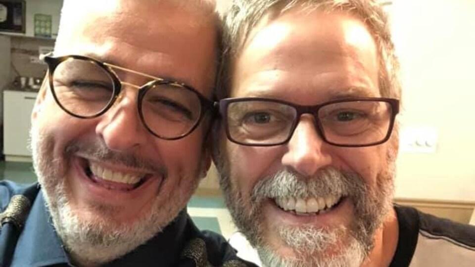 Les deux hommes sourit à la caméra.