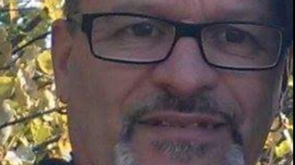 Photo cadre serré du visage de Denis Picard. Il porte des lunettes et une barbichette.