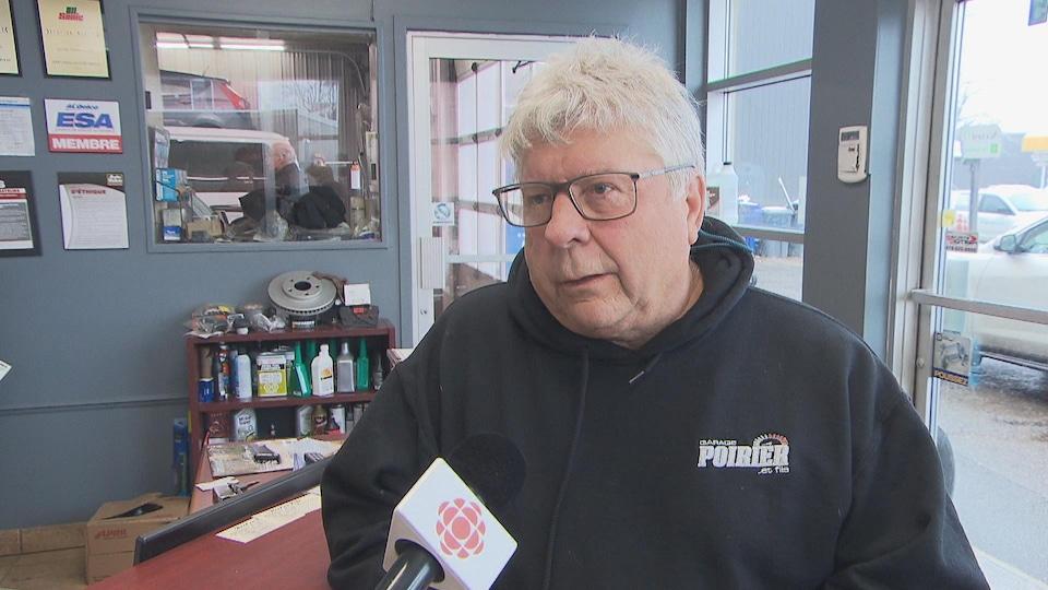 Denis Poirier au micro de Radio-Canada dans le garage