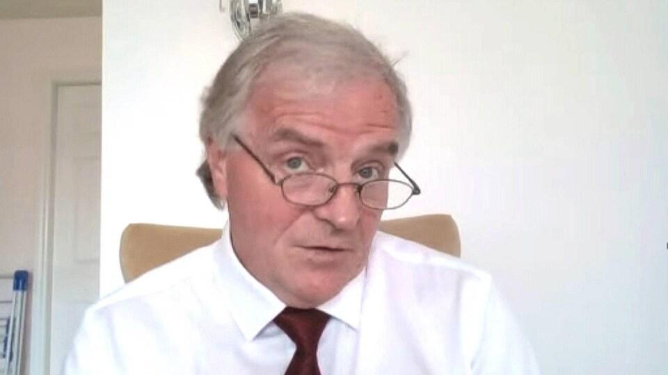 Un homme en chemise blanche et cravate devant une webcam.