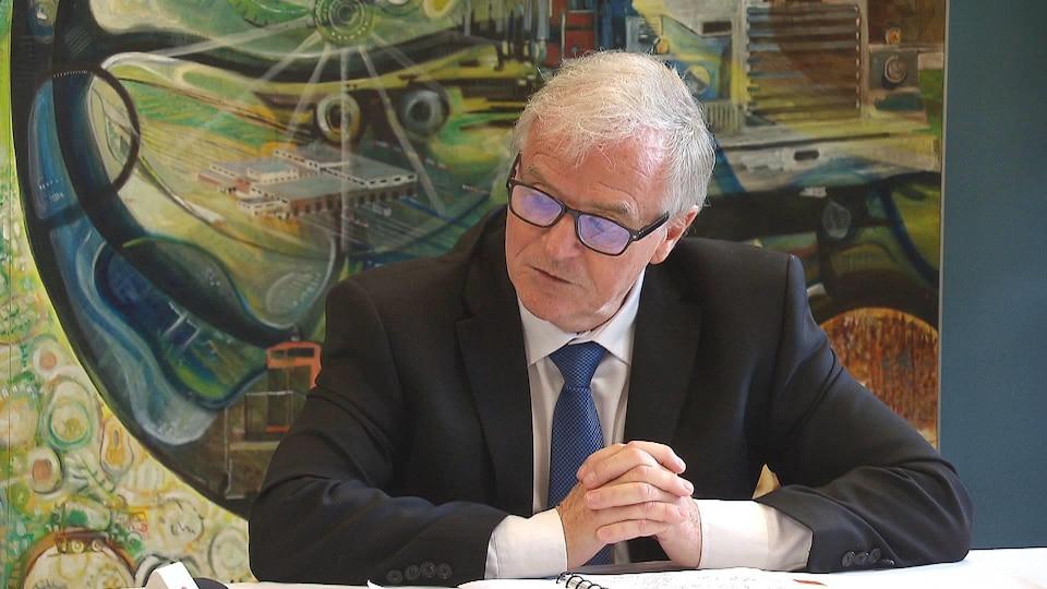 Denis Prud'homme assis devant des documents.