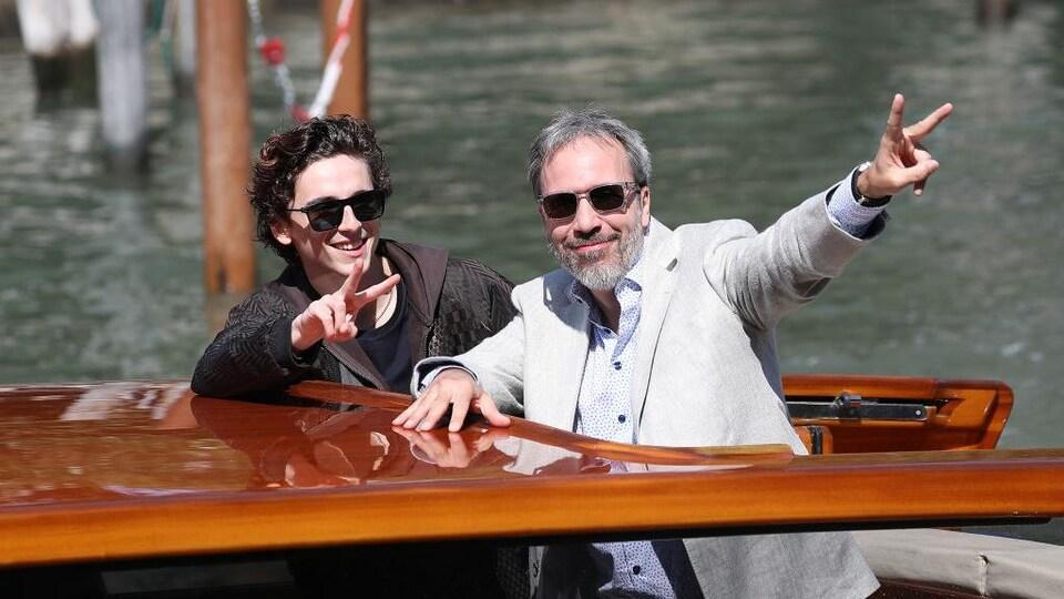 Deux hommes sont sur un bateau et saluent la foule.