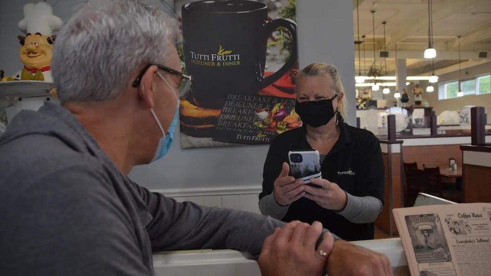 Denise Boyer tient un téléphone intelligent.