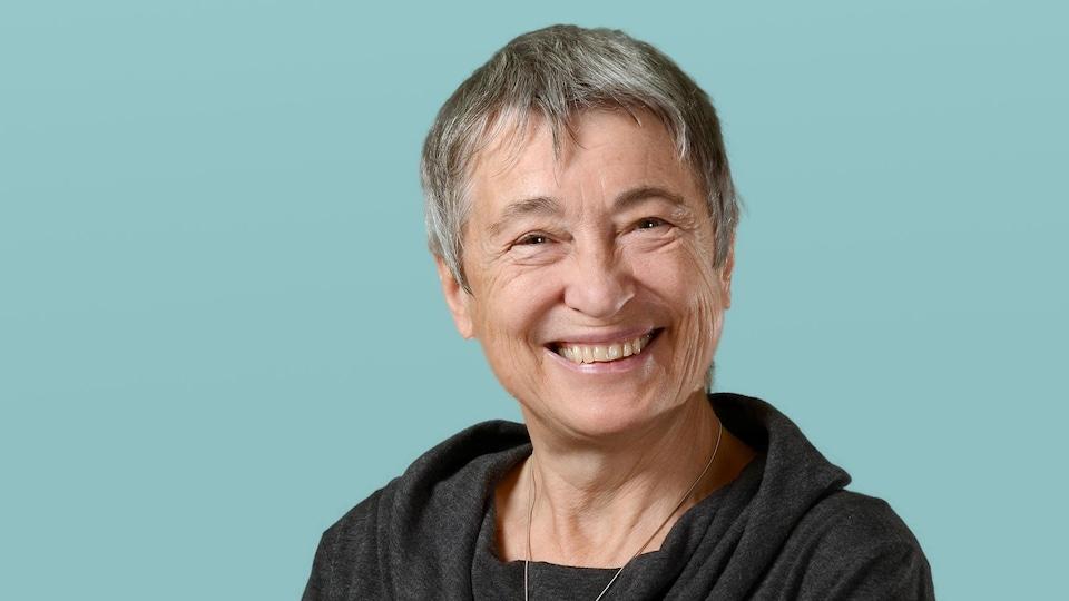 Une femme de 73 ans sourit à la caméra.