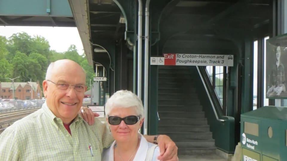 Dennis Anderson et sa femme sont bras dessus bras dessous, sur le quai d'une gare.