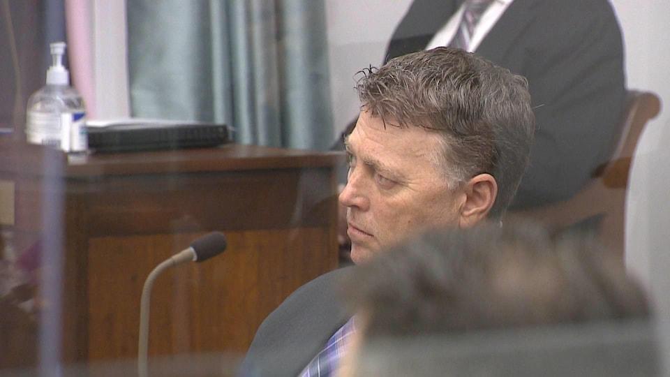 Dennis King est assis et écoute le discours.