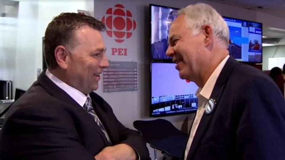 Deux hommes face à face discutent amicalement.