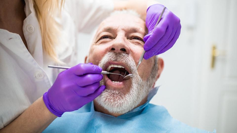 Homme d'un certain âge sur la chaise du dentiste, la bouche ouverte.