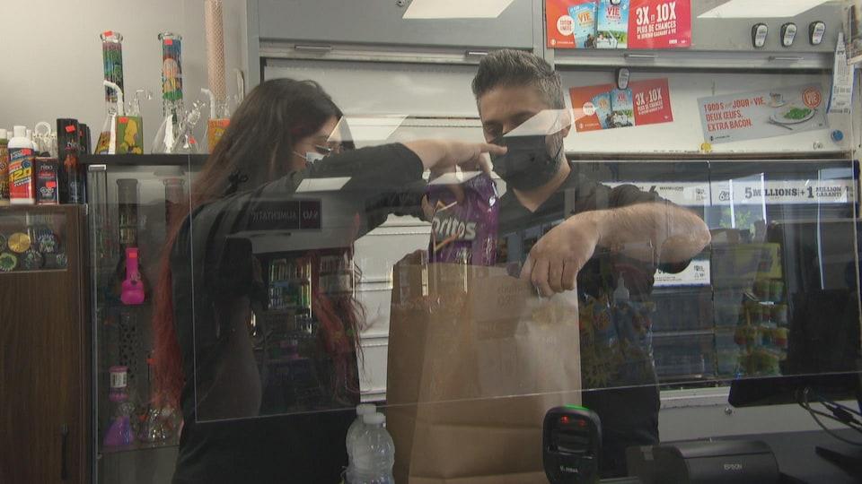 Des employés mettent des items dans un sac.