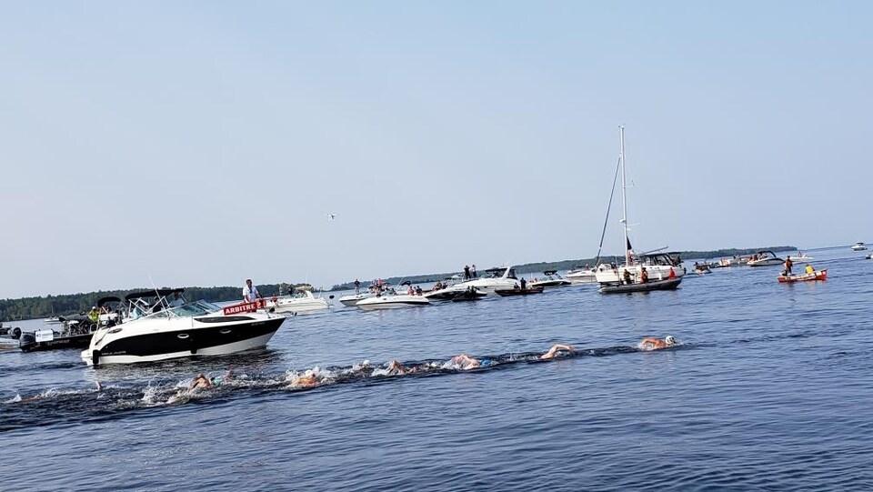 On voit les nageurs amorcer leur traversée avec les bateaux qui les accompagnent.