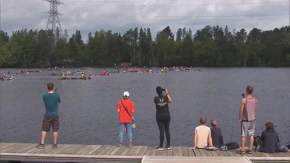 Des gens debout sur un quai qui regardent les participants ramer en canot sur la rivière Saint-Maurice.