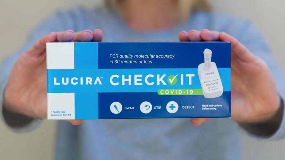 Une femme tenant dans ses mains un kit d'autodépistage de la marque Lucira Health