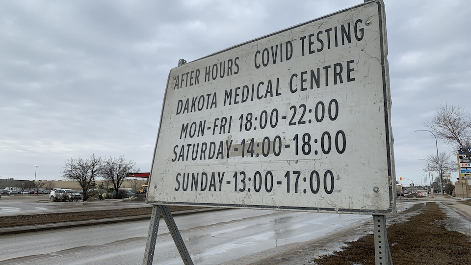 Une pancarte près de la rue avec des informations qui indiquent que c'est un centre de dépistage de la COVID-19.
