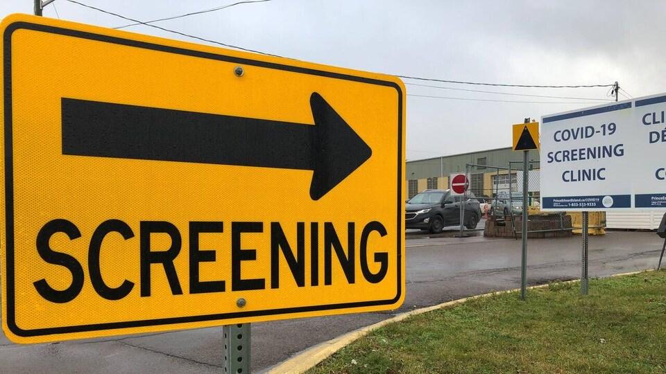 Une pancarte jaune avec une flèche pointant vers un bâtiment.