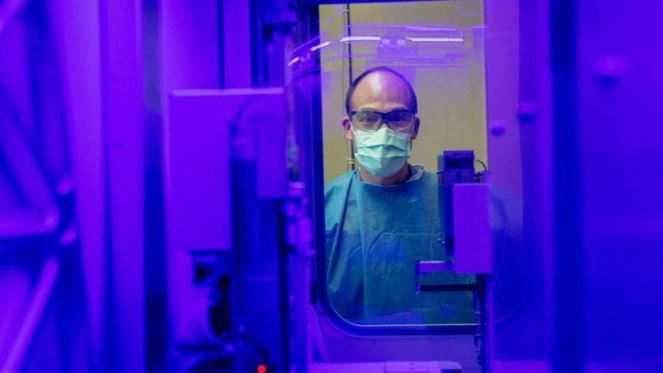 Un homme vêtu d'un sarrau, le visage couvert d'un masque et portant des lunettes de protection est photographié dans un laboratoire de microbiologie.