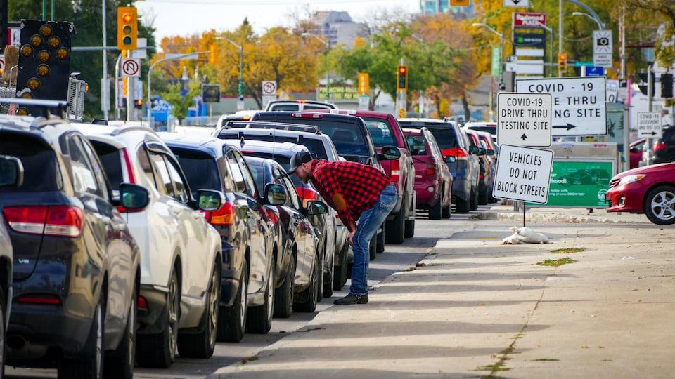 Des gens dans leur voiture sont dans une longue file pour se faire dépister.