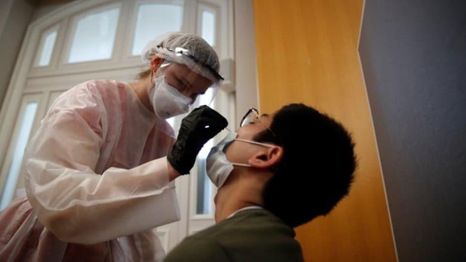 Une infirmière en combinaison de sécurité avec masque et charlotte et gants fait un test de dépistage à la covid-19 à un homme.