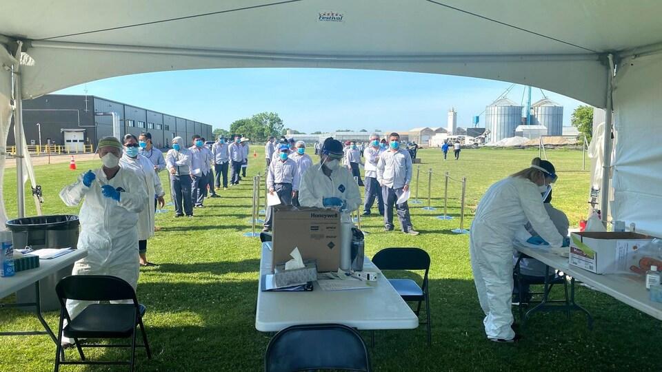Des gens font la file devant une tente. Ils portent des masques. Du personnel médical fait des tests sous la tente.