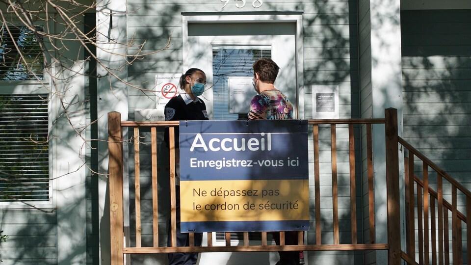 Deux personnes attendent devant la clinique de dépistage de La Pocatière, en mars 2021.