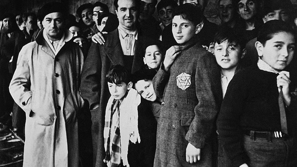 Sur cette photo de 1942, des hommes et des enfants regardent la caméra.