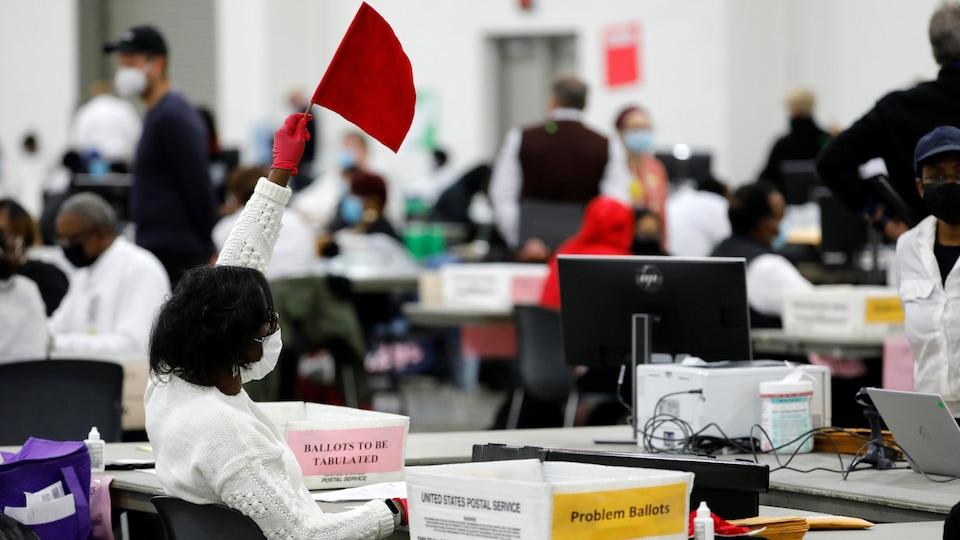 Une femme masquée lève un drapeau rouge au milieu d'une salle où des votes sont dépouillés.