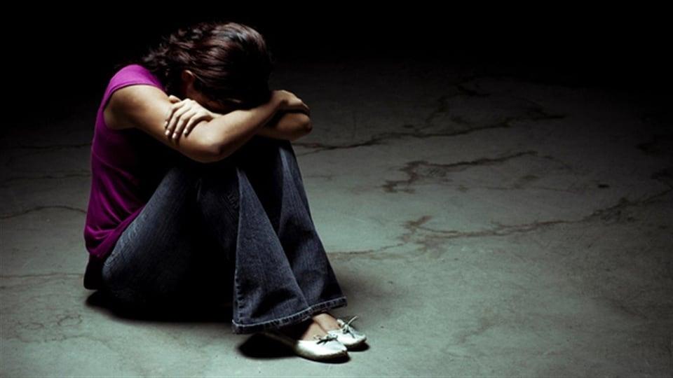 Une femme déprimée assise sur le plancher.