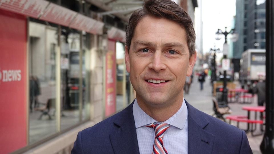 M. Amos sourit à la caméra sur une rue d'Ottawa.