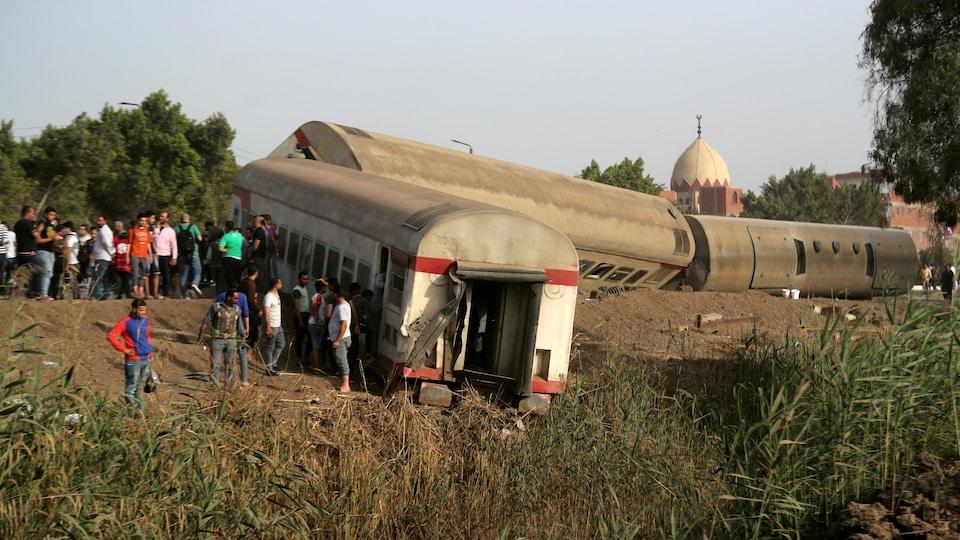 Des gens se tiennent à proximité de trois wagons qui ont déraillé.