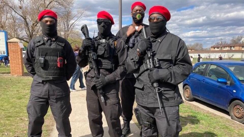 Quatre hommes masqués, portant des habits militaires noirs ainsi qu'un béret rouge, posent pour la photo. Deux d'entre eux ont un fusil mitrailleur.